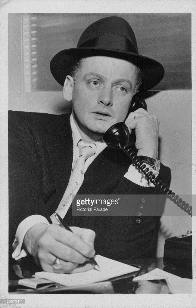 Portrait of actor Art Carney, answering the telephone and wearing a black suit and hat, circa 1950-1960.