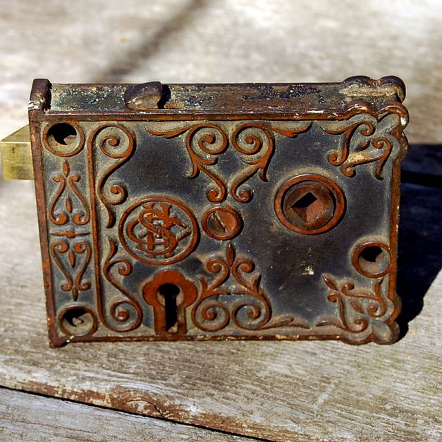 Antique Rim Lock~  This ornate antique metal rim lock (or lock box) is one of the earliest types of door locks made in America. The lock is fastened to the face of the door, so the beautiful scrolls on its surface are visible.