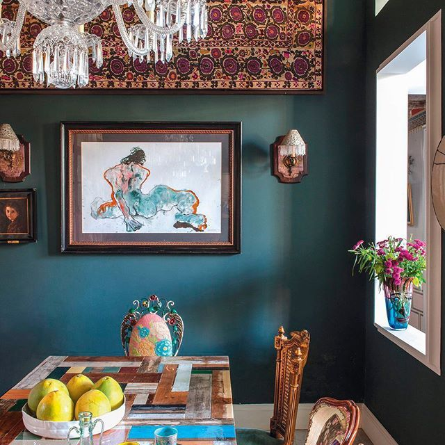 In the dining room of a home in Beirut, a Saint-Louis crystal chandelier hangs over a table by Piet Hein Eek. The sterling silver sconces are Victorian, the antique suzani wall hanging is from Uzbekistan, the wall paint is by Tinol, and the watercolor is by Lebanese artist Marwan Sahmarani. | Photo: Guillaume de Laubier; Design: Maria Hibri