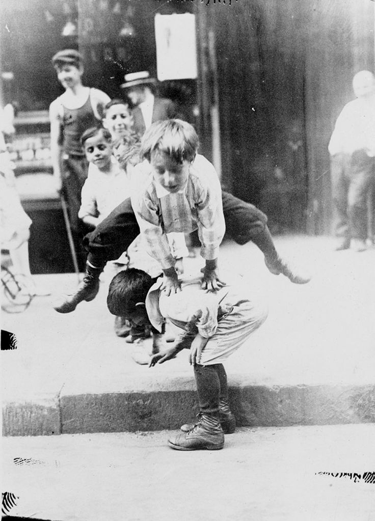 Kids playing leap frog on a street, New York, 1900s