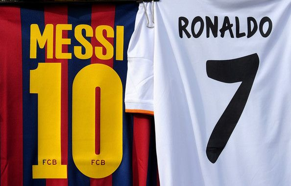 Shirts bearing the names of Lionel Messi of FC Barcelona and Cristiano Ronaldo of Real Madrid CF are seen on display at a merchandise stall prior to the La Liga match between Real Madrid CF and FC Barcelona at estadio Santiago Bernabeu on March 23, 2014 in Madrid, Spain.