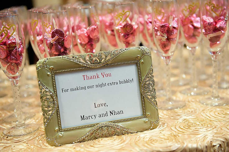 Champagne flute favors were filled with pink candy Hershey kisses and their names and date in gold.