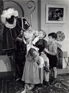 DUTCH: Haarlem 3 december 1949. Sinterklaas en Zwarte Piet met drie kinderen in huiskamer. Het jongetje met donker haar en korte broek is de beroemde Haarlemse zanger: Boudewijn de Groot.