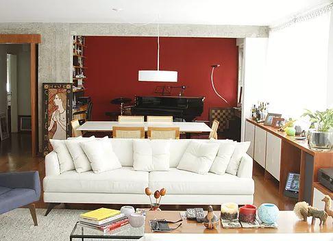 Sala de estar integrada com sala de jantar e sala de música. Vigas e pilares no concreto aparente, parede vermelha, pendente sobre mesa de jantar, cortinas de tecido.