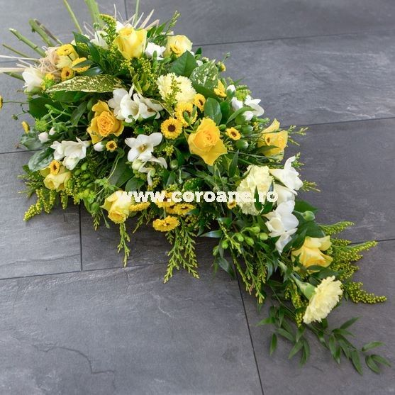 Jerba funerara cu un singur capat, in forma de lacrima, decorata cu trandafiri galbeni, santini si frezii, puse in evidenta si sustinute de un mix de verdeata proaspata.