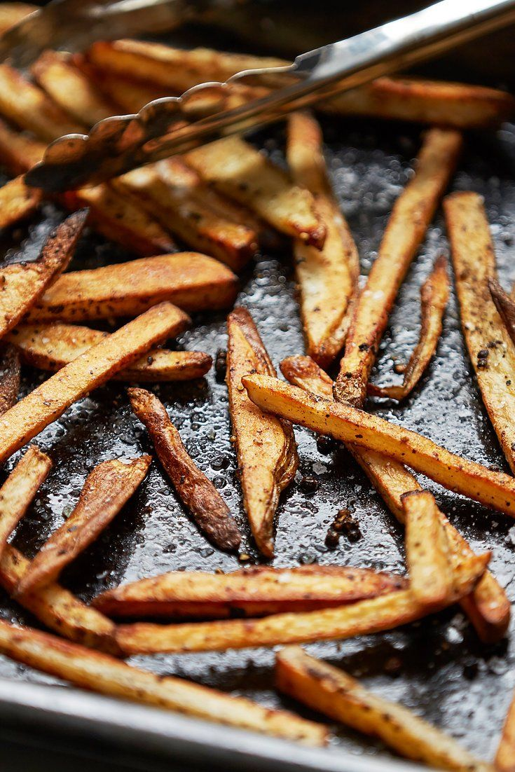 """NYT Cooking: If every baked French fry you've ever eaten has been a soggy disappointment, then this recipe is for you. The key to achieving perfectly crisp """"fries"""" is heating your sheet pan in a 500-degree oven for a good 10 minutes. When you toss the potatoes onto the blisteringly hot pan, magic happens: The potatoes sear and develop a truly crunchy crust. In terms of seasoning, we keep it simple with just..."""
