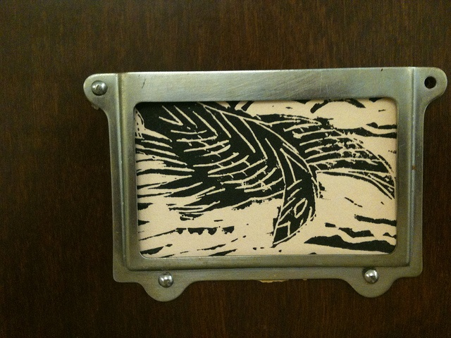 A small linocut of a black bord descending from the sky.