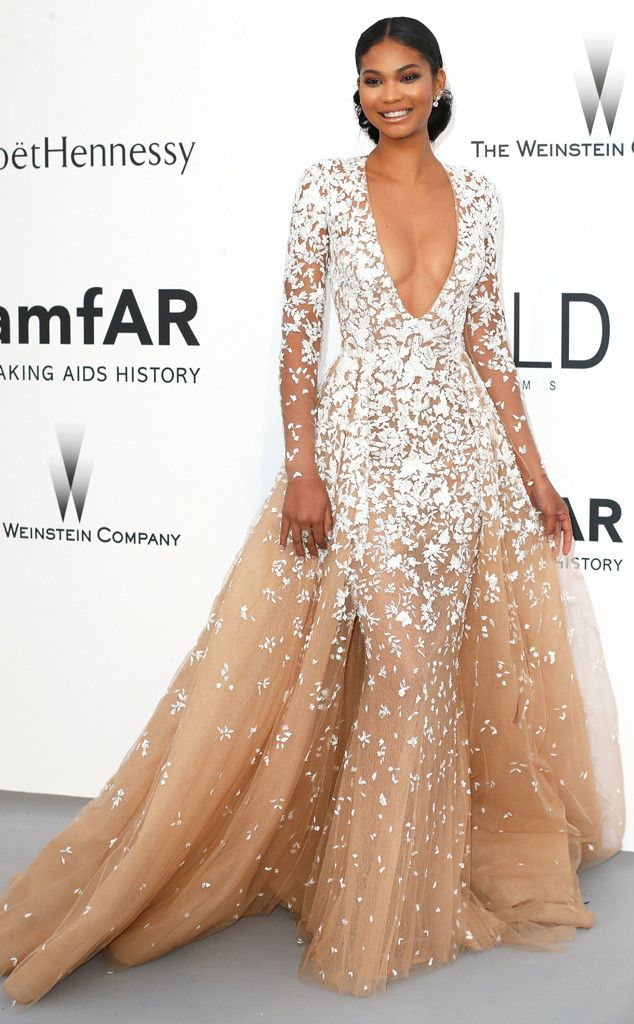 2015 AMFAR GALA: STAR ARRIVALS AT THE CANNES BENEFIT CHANEL IMAN The supermodel makes a breathtaking appearance in a plunging Zuhair Murad Couture gown featuring white floral details and a billowing skirt.