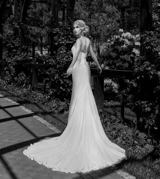 A fitted mermaid silhouette wedding dress. A sweetheart neckline in the front. The back is closed, V-shaped cutout. Stretch crepe is decorated with handmade embroidery and beads. The skirt has a train.