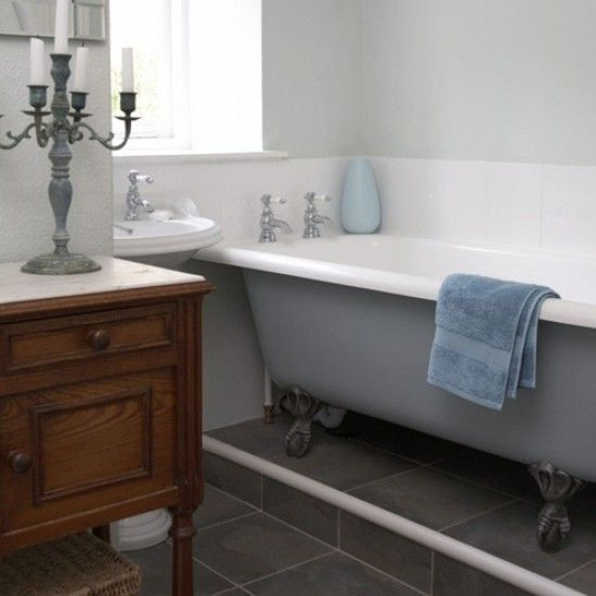 TranQUiL BaThr00m  The elegant roll-top bath sets the scene in this relaxing bathroom. The cherry-wood chest looks great against the soft blue walls and white tiling, and a wicker hamper is used for extra storage. Vintage candle holders complete the look and create a romantic feel.