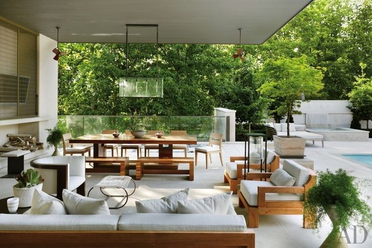 28 Luxurious Indoor-Outdoor Rooms Photos | Architectural Digest [A poolside lounge at a Nashville, Tennessee, home features a pendant lantern by Ames Ingham and a barrel-back chair from Dennis Miller Assoc.; the Robert Bristol dining table and benches are from Ralph Pucci International, and the cushions on the sofa, lounge chairs, and dining chairs are covered in a Perennials fabric.]