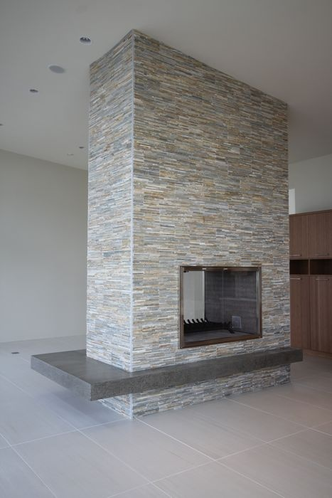 Gas fireplace, stone veneer finish with a cantilevered polished concrete hearth & custom built stainless steel doors