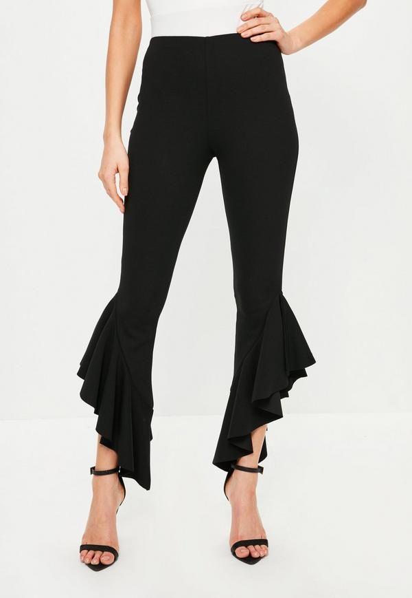 Los pantalones de pinzas están de moda.  En negro y con volantes en los bajos.