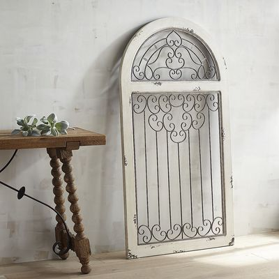 Hanging an arched window is tricky stuff. Hanging our window-like antiqued white arch? Pretty simple. More of an architectural element than a simple wall hanging, its rustic wooden frame encases Spanish-style scrolled wrought iron worthy of a Mediterranean villa.