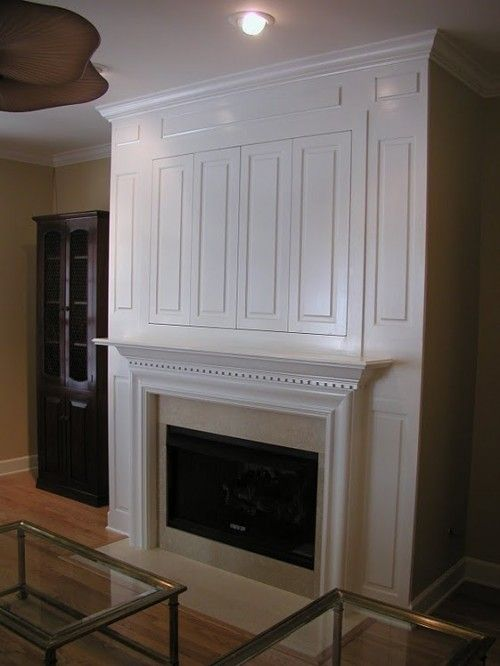 Hide a flat screen TV behind millwork paneling over the fireplace -- LOVE how this looks!