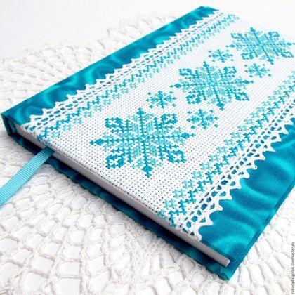 Купить или заказать Блокнот для записей 'Снежинка' в интернет-магазине на Ярмарке Мастеров. Блокнот ручной работы, выполнен 'с нуля'. 80 листов прошиты в книжный переплет. Страницы белого цвета с разлиновкой и угловой виньеткой с рисунком снежинок. Форзацы - плотная бумага с цветной лазерной печатью в тон обложки. Каптал прошит вручную нитками в тон обложки. Закладка - репсовая лента. Обложка - переплетный картон, оклеенный х/б тканью, декорирована х/б кружевом и ручной вышивкой крестом.