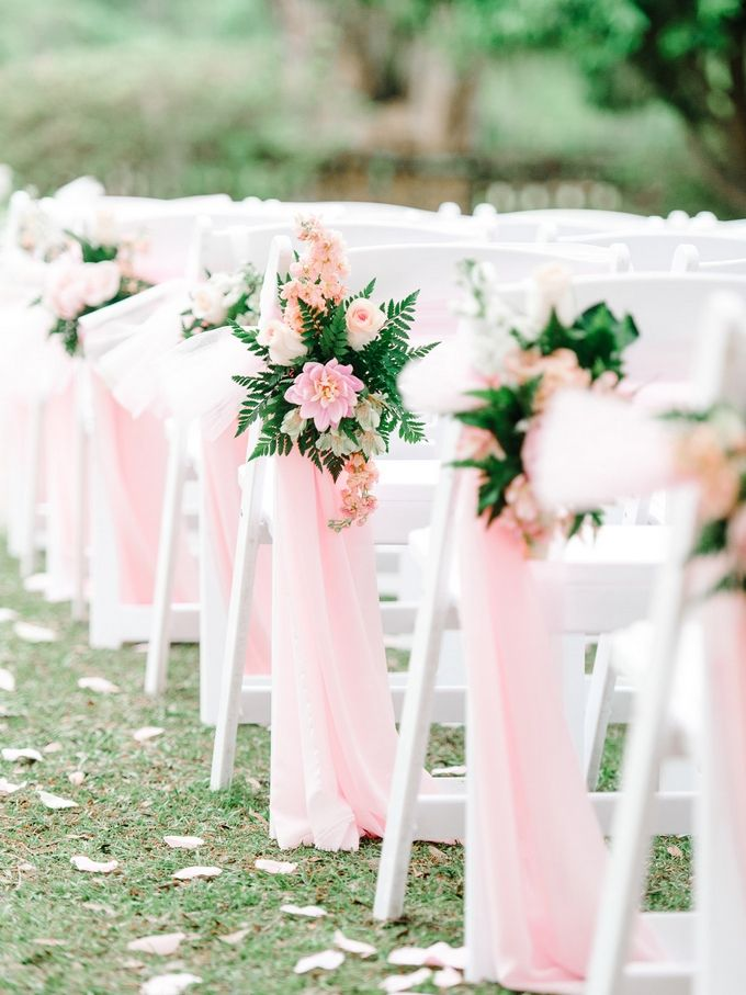 Pink flowing fabric and fun floral arrangements are a thoughtful addition to the chairs lining the ceremony aisle.
