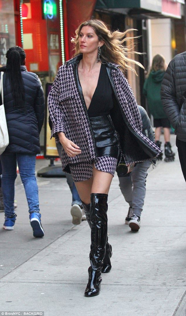 Gal on the go: She heightened the effect of her gams by slipping into a pair of gleaming black boots that stretched up over her knees