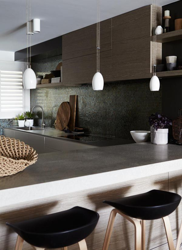 Lovely horizontal wood-grained cabinets, along with a dark iridescent backsplash, makes a moody textural kitchen theme.