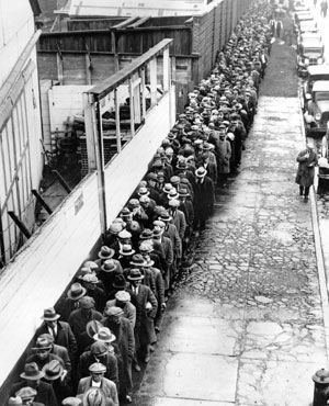 This is an image of Canadian men standing in an unemployment line, hoping for work. This source is credible as it is an image taken of unemployed Canadian men during the time of the Great Depression. This tells us about the changing lives of Canadians at the time because the Great Depression was a harsh contrast to the Roaring 1920s. Unemployment meant that life during the Great Depression would be very difficult, as lavish lifestyles had to change.
