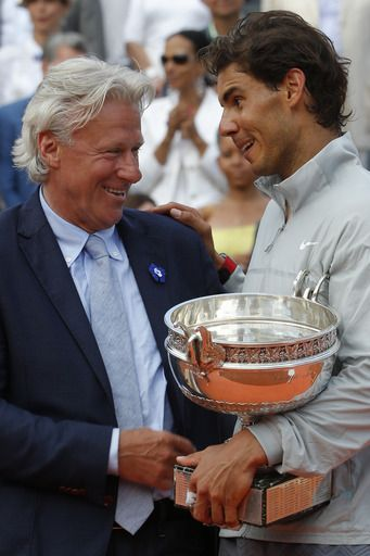 Spain's Rafael Nadal holds the trophy as he talks to Swedish tennis legend Bjorn Borg after winning the final of the French Open tennis tournament against Serbia's Novak Djokovic at the Roland Garros stadium, in Paris, France, Sunday, June 8, 2014. Nadal won in four sets 3-6, 7-5, 6-2, 6-4. (AP)