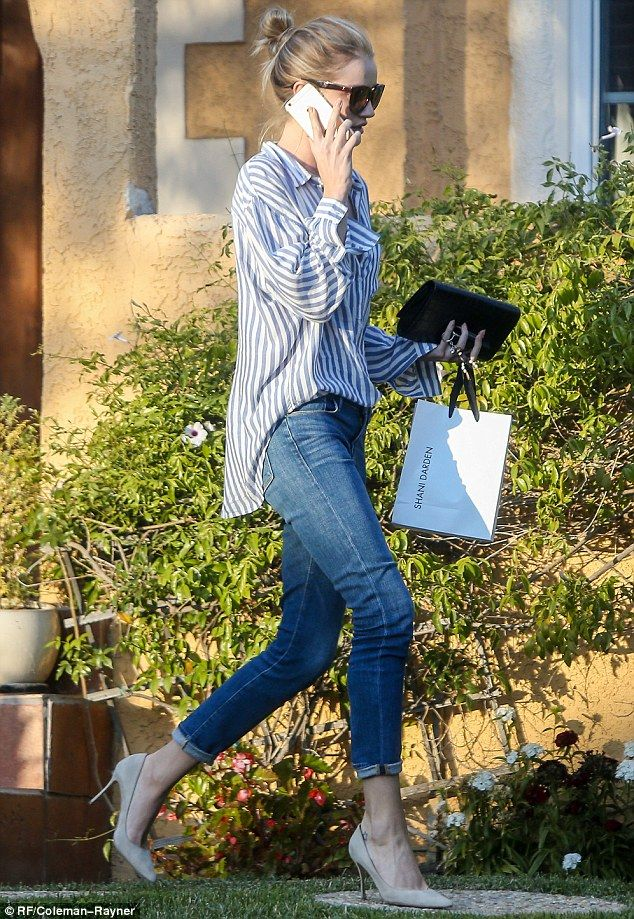 Hanging out: Rosie was chatting on her phone as she left a friend's house with a bag of goodies
