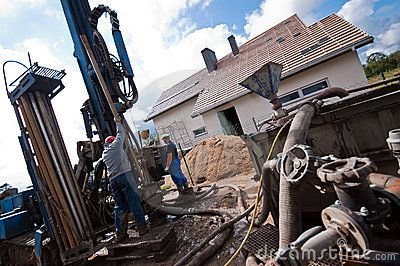 Two workmen using geothermal drilling machinery outside modern house or home.