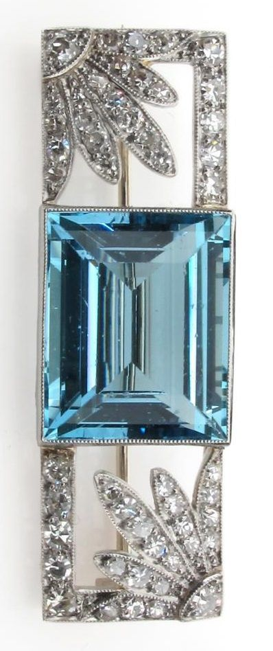 An Art Deco aquamarine and diamond brooch, the baguette shaped aquamarine is millegrain set between two diamond set flower-head sections within rectangular diamond set border.