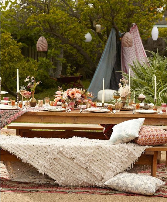 Lots of candles, small floral arrangements, plus loads of comfy throws and pillows make this an inviting, lively space.  Scott Clark Photo via 100 Layer Cake