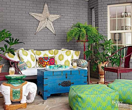 An advantage over large patios, small patios can feature bright colors without overwhelming the eye. Here, a mix of bright greens and blues are a stunning complement to the home's gray exterior walls. Backless ottomans matching the decor provide extra seating without interfering with sight lines.