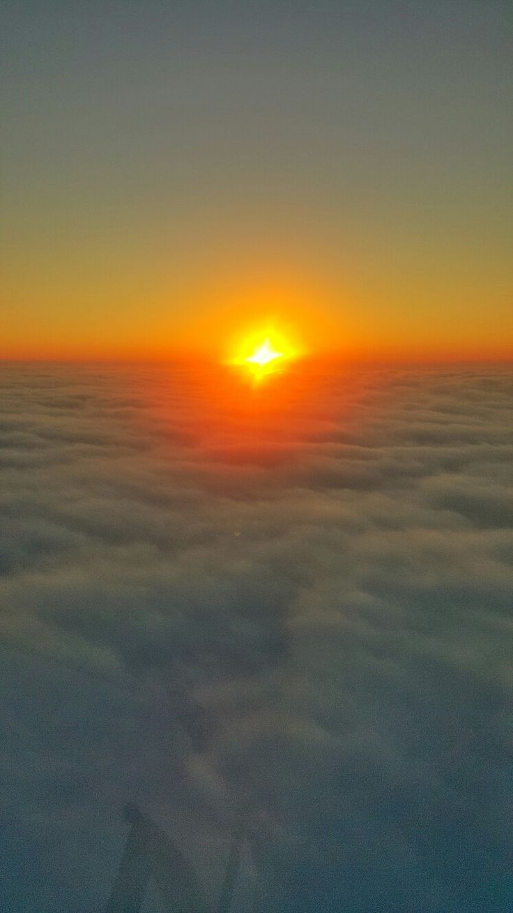 Sunset over the clouds on board