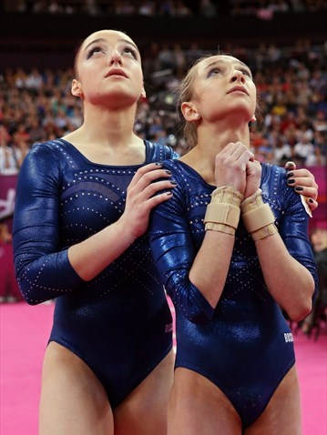 Russia's Aliya Mustafina and Victoria Komova wait for the final scores
