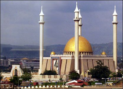Debating which won the competition for highest spire in Abuja--the Christian church or the mosque. Men.