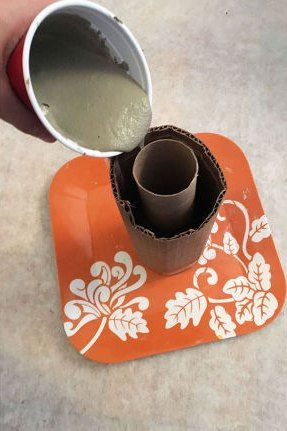 She carefully pours cement into a toilet paper tube. What it becomes? Gorgeous decorating hack!