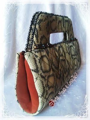 Esta bolsa carteira é uma criação feita em tecido com estampa de cobra, a lateral em tecido fino vermelho dá um charme especial:^>