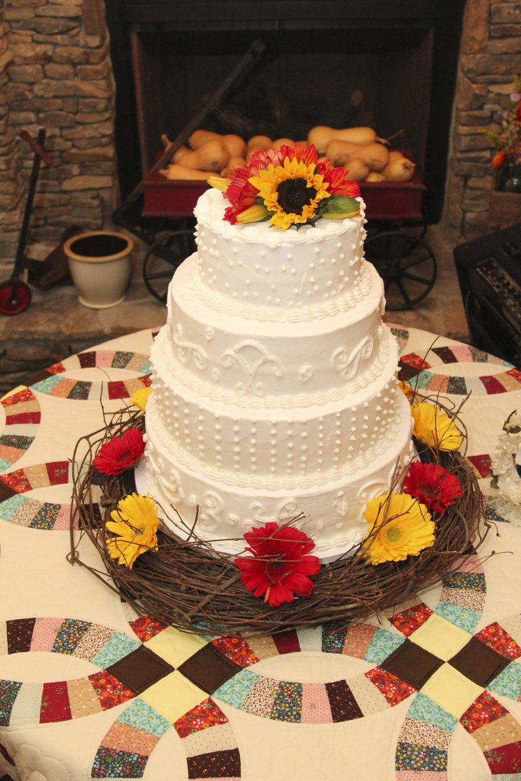 A three tiered white cake with intriquite designs, sunflower and gerber daisy accents, and a grapevine wreath, resting upon a vintage multicolored country quilt.  Photo by 5 Petal Productions