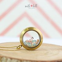 FLAMINGO LOCKET Be a flamingo in a flock of pigeons with this elegant look. This dazzling locket features a Large Matte Gold Locket, a fun pink Flamingo charm, three Pacific Opal Crystals and three Cream Rose Pearls
