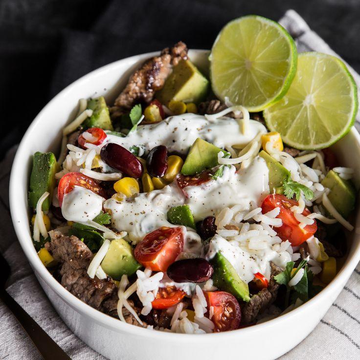 In diese köstliche Burrito Bowl kommen zu den zarten Rinderstreifen noch Reis, Mais, Avocado, Bohnen, Tomaten und ein frisches Joghurt-Limetten-Dressing.