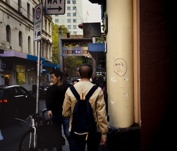 "China Town, Melbourne - 03/05/2016 - Georgia Urquhart --- I love this, one because the guy is wearing a jacket that's the same colour as the pole. and two because the pole says ""cute boys"" on it right next to his head hahah. I also enjoy how the guy is centred, making your eyed be drawn to him first [which is what i was going for (not often that happens with me)]."