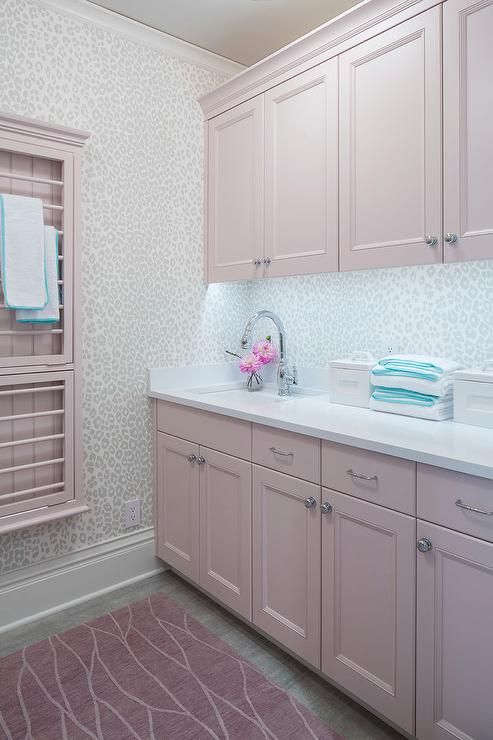 Pink laundry room features pink cabinets paired with white quartz countertop and a leopard print wallpaper as backsplash, Thibaut Fabric Animal Print Wallpaper.