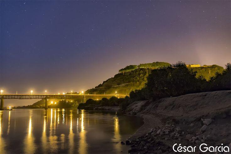 Um cenário nocturno captado a partir da margem do rio Tejo, na Ribeira de Santarém, com a Ponte D.Luís e o esporão da Alcáçova de Santarém em fundo.