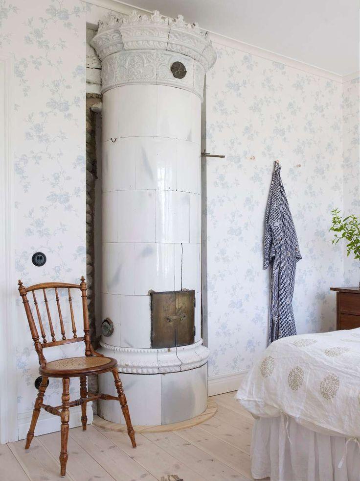 Huset har flera fina gamla kakelugnar, som här i sovrummet. Tapet, Rosen, från Lim & Handtryck.