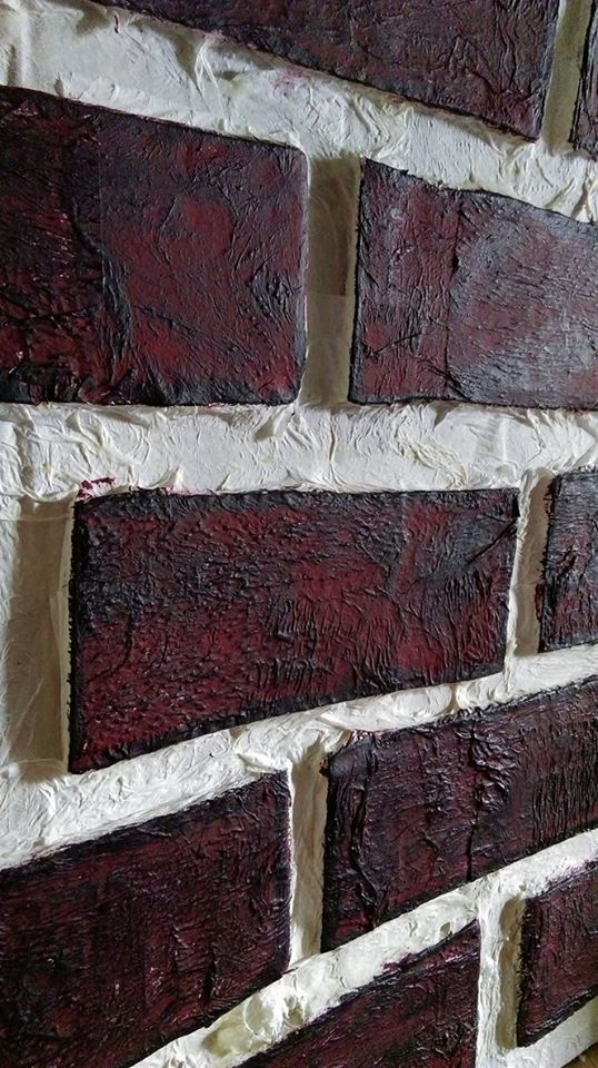 Humpty Dumpty's Wall.   The 'wall' is a cardboard box. Bricks are rectangles of cardboard stuck onto the box, papier mache over the top with white kitchen towel. The bricks are painted with burgundy paint. When dry, use a sponge and a VERY SMALL AMOUNT of black paint lightly wiped over the bricks to highlight the texture and give a realistic look.