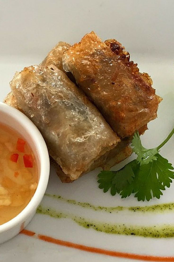 Vietnamese Fried Spring Rolls - These delicate crunchy fried appetizers will make you wonder why you used to love fried egg rolls. Served with a sweet chili dipping sauce and fresh herbs. The perfect starter for your Asian inspired meal at home.