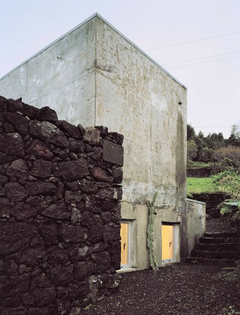 Take a look inside this modern concrete house slotted behind the crumbling stone walls of a ruined building.