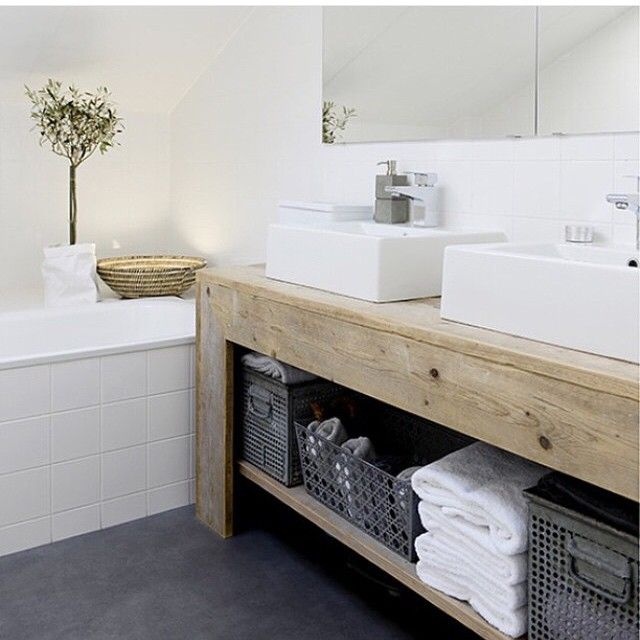 Open wooden shelves and white sinks for the bathroom