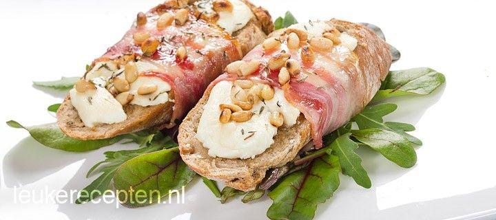 Smakelijk voorgerecht van stokbrood met geitenkaas en pijnboompitten omwikkeld met spek