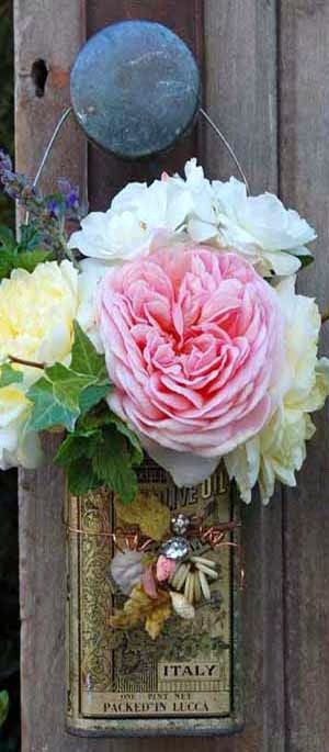 Garden roses in old embellished olive oil can ~ what a nice touch for the garden shed door!