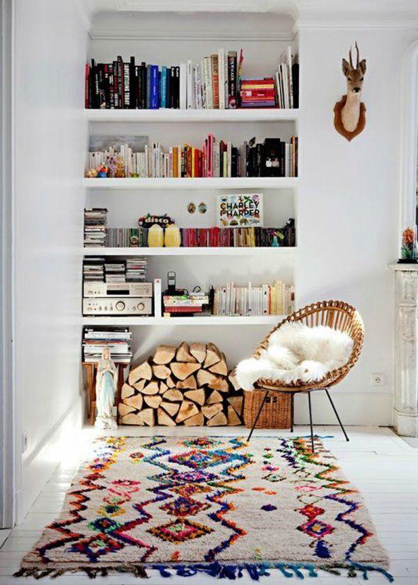 """Pour une ambiance """"maison de campagne"""", les bûches empilées, le fauteuil couvert d'une peau de bête et les livres rangés dans la bibliothèque murale constituent une douce ambiance hors du temps. Pour l'esprit kinfolk, on a le tapis Kilim haut en couleur et frangé qui donne du cachet à l'espace, sans oublier ce trophée fixé au mur. Entre esprit nature et style sophistiqué, on obtient une déco folk colorée et minimaliste."""