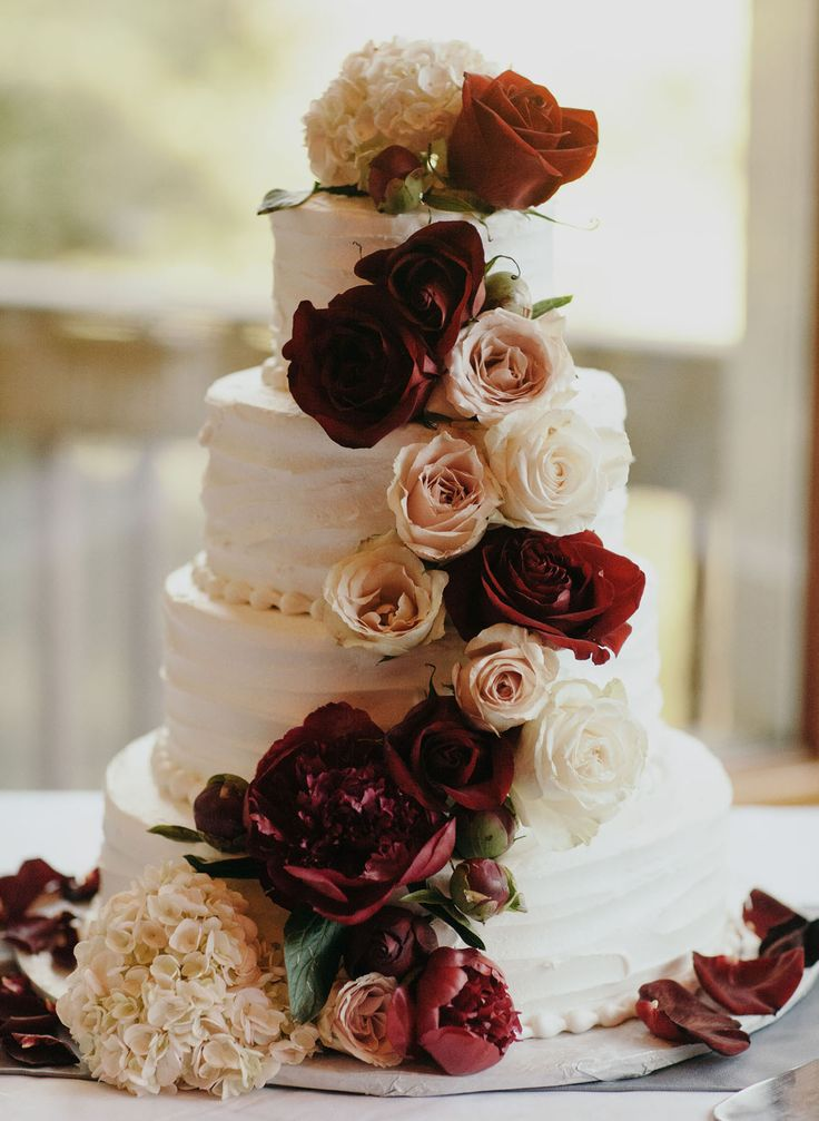 Four-tier ruffled cake with burgundy roses